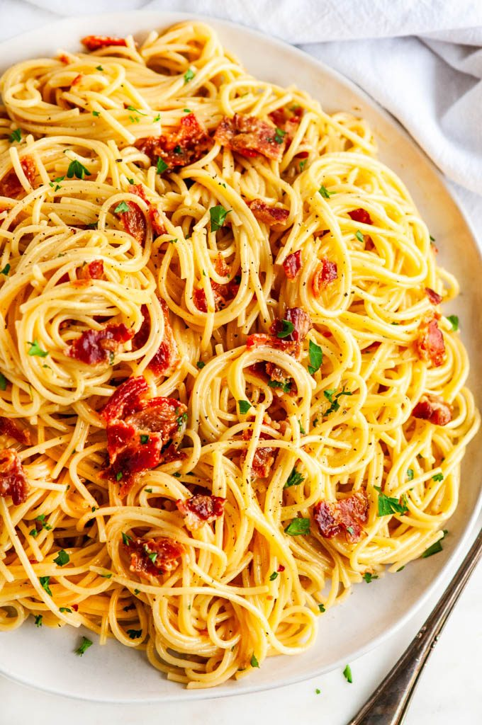 Classic Spaghetti Carbonara on light gray plate and white marble