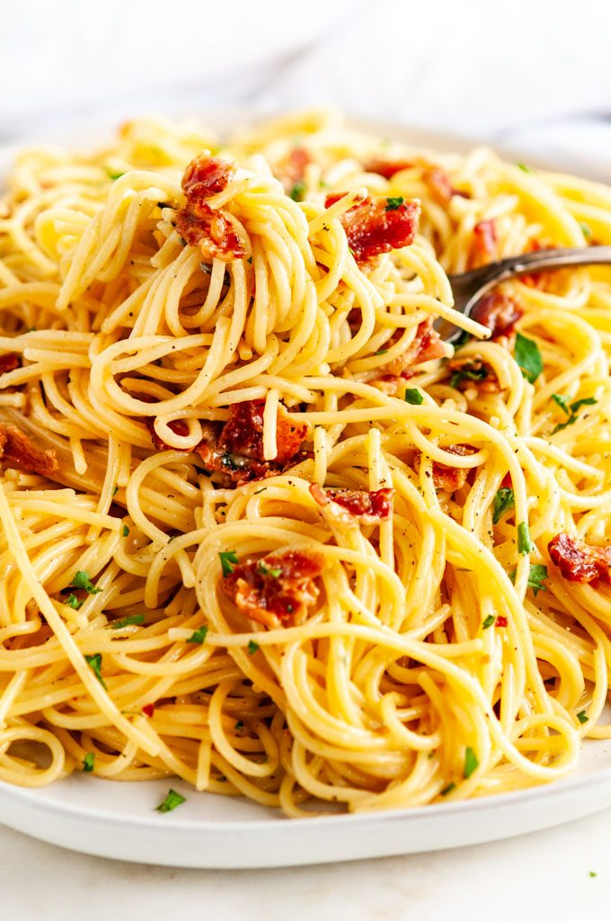 Classic Spaghetti Carbonara on light gray plate and white marble with antique silver spoon