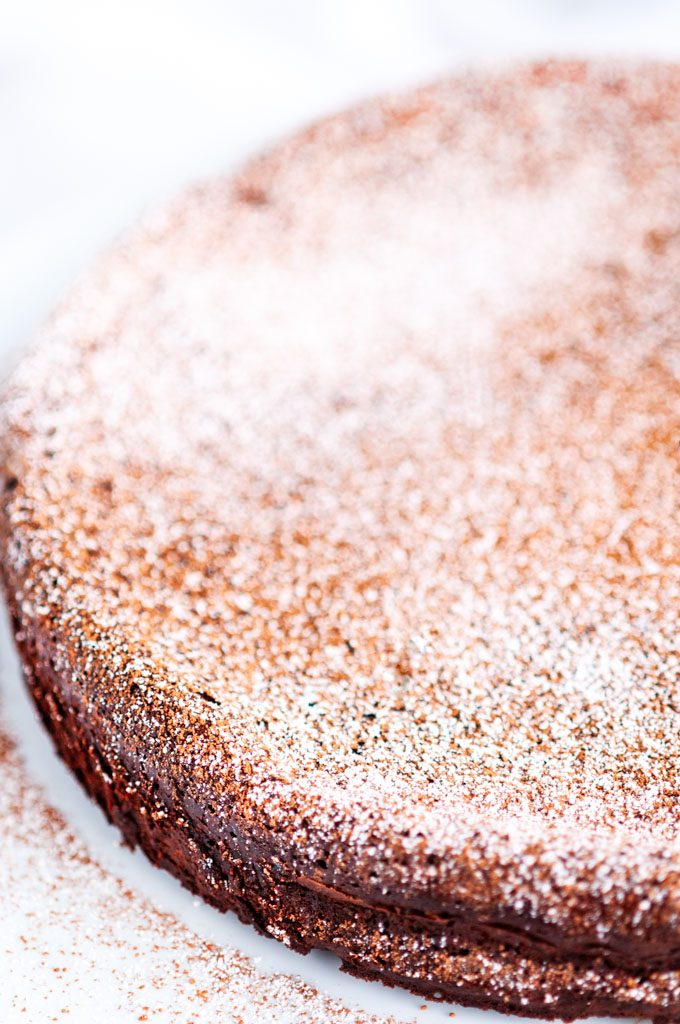 Flourless Chocolate Torte dusted with cocoa powder and powdered sugar on white marble