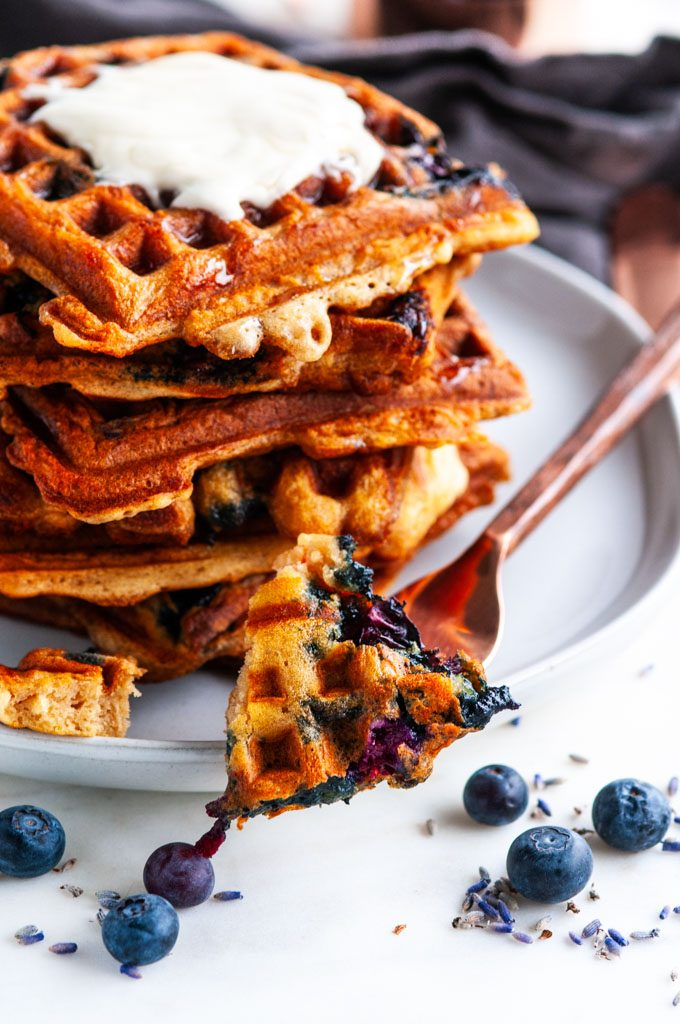 London Fog Blueberry Waffles bite with copper silverware and gray tea towel