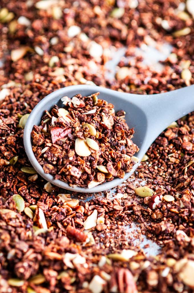 Chocolate Ancient Grains Nut Granola with gray stirring spoon on sheet pan