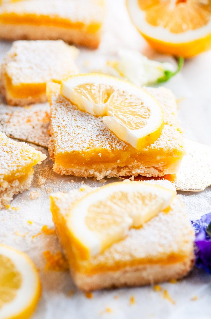 Best Ever Classic Lemon Bars with gold pie server and edible purple and white flowers close up