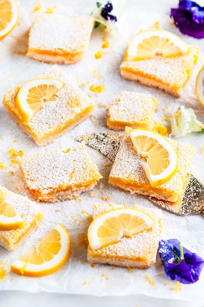 Best Ever Classic Lemon Bars with gold pie server and edible purple and white flowers