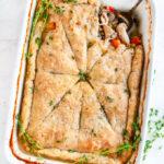 Chicken wild rice pot pie in white baking dish with antique fork