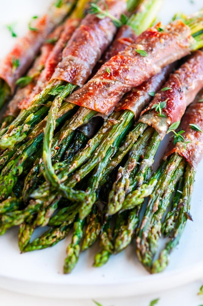 Garlic Parmesan Prosciutto Wrapped Asparagus close up on light gray plate