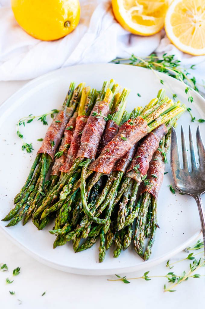 Garlic Parmesan Prosciutto Wrapped Asparagus on light gray plate with antique silver fork