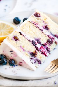 Lemon Blueberry Lavender Cake with Mascarpone Buttercream Frosting slice on white plate with gold fork