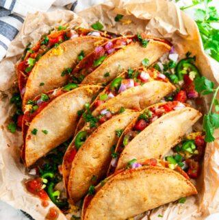 Cheesy Potato Tacos on brown parchment paper with cilantro, tomato, onion, and salsa
