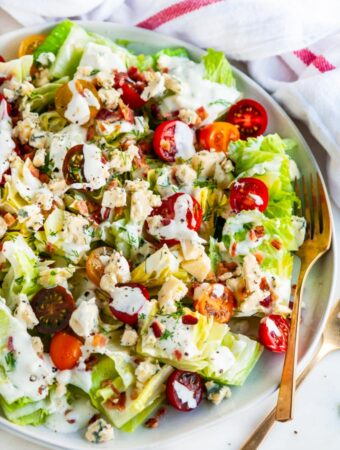 Chopped wedge salad on gray plate with gold fork