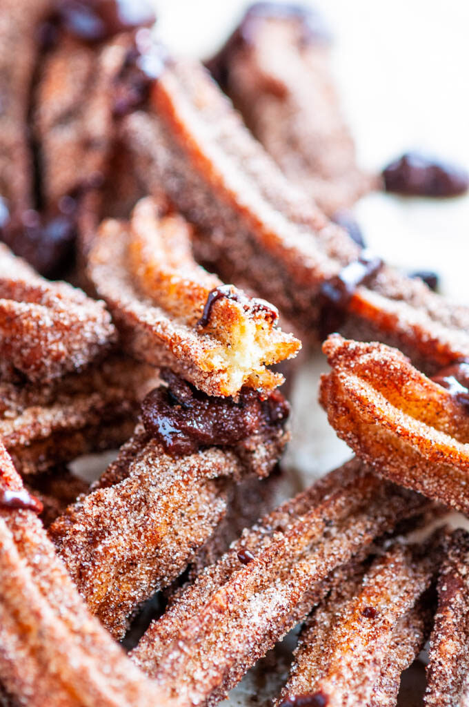 Homemade Churros with Mexican Dipping Sauce on brown parchment paper