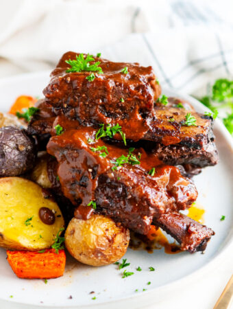 Mole braised beef short ribs on gray plate with roasted potatoes and tea towel
