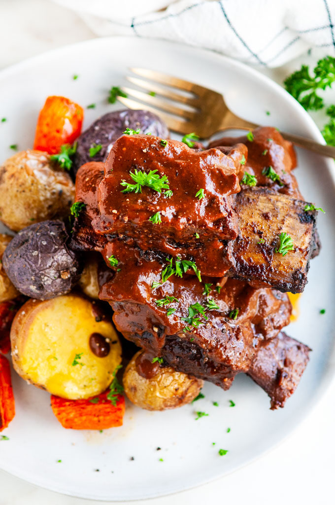 Mole braised beef short ribs on gray plate with roasted potatoes and gold fork