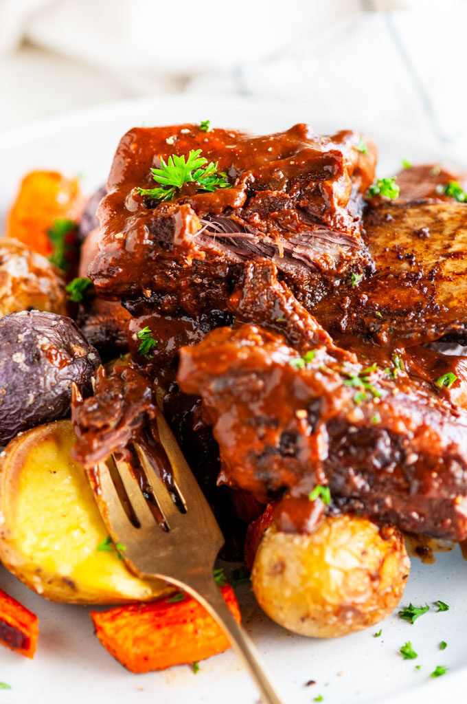 Mole braised beef short ribs and roasted vegetables on gray plate with gold fork