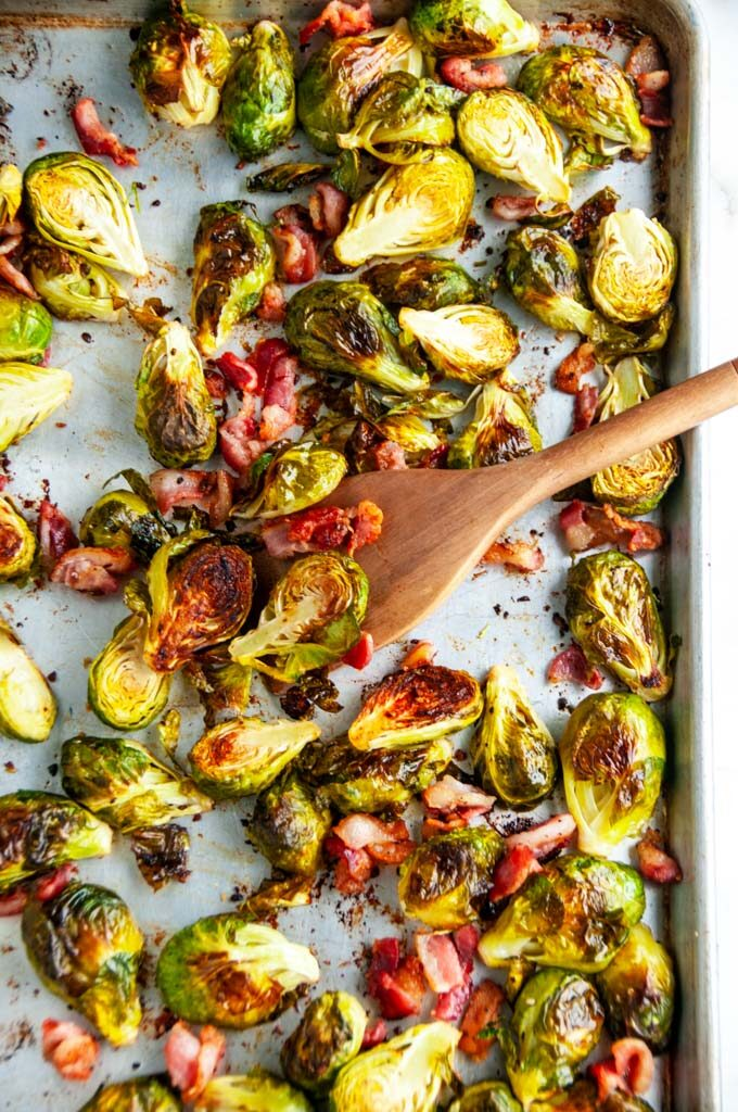 Sheet Pan Bacon Garlic Brussels Sprouts on a sheet pan with wooden spoon