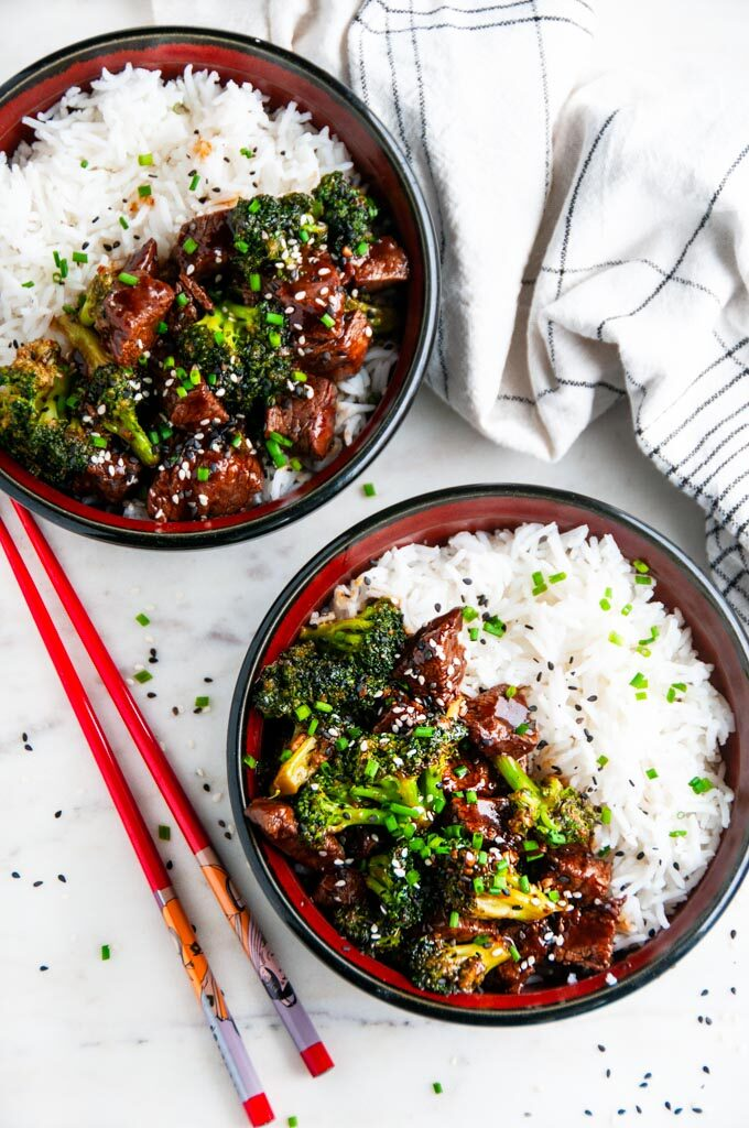 Skillet Beef and Broccoli in black and red bowls on marble with chopsticks and tea towel