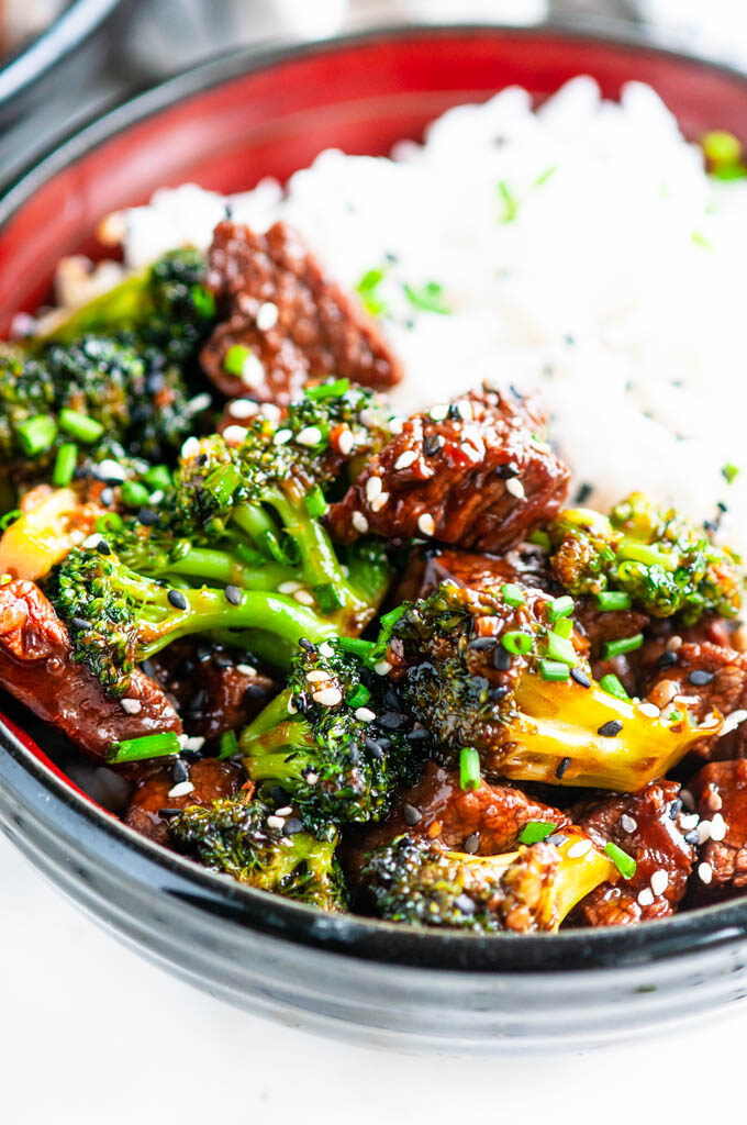 Skillet Beef and Broccoli in black and red bowls on marble close up