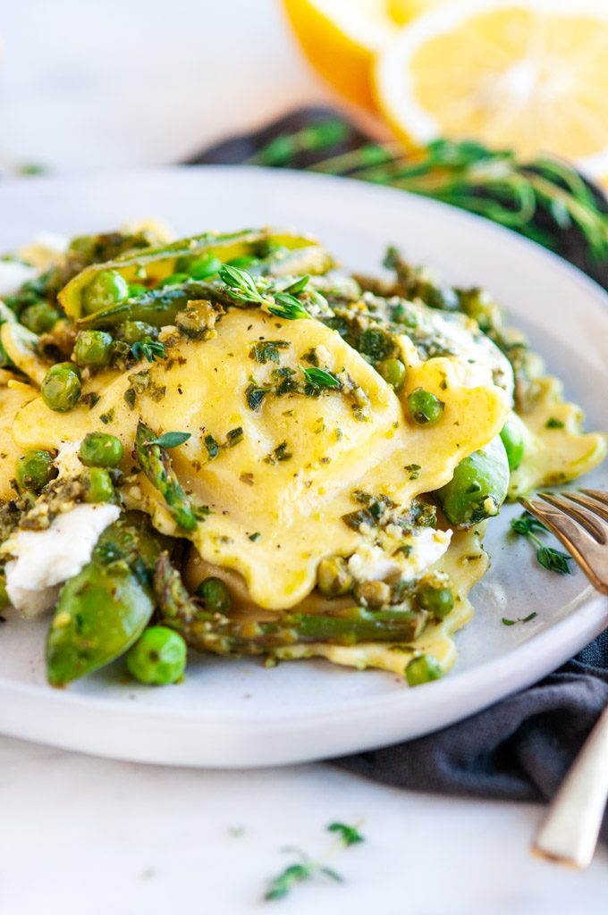Spring Pea Asparagus Ricotta Ravioli on gray plate with lemons and gold fork