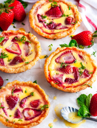 Strawberry Custard Honey Tarts with Lemon Curd on parchment paper with fresh mint