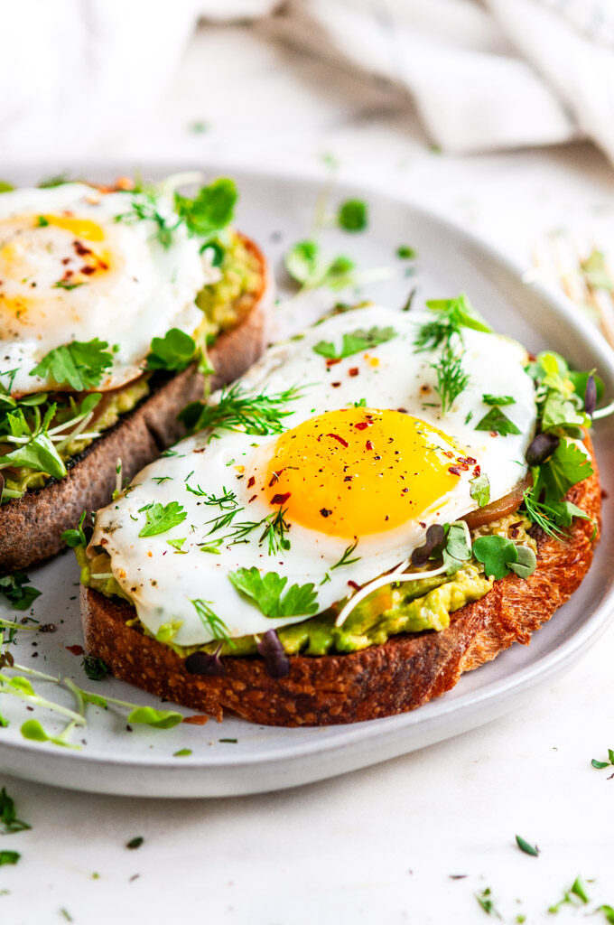Avocado egg breakfast toast on gray plate with gold fork