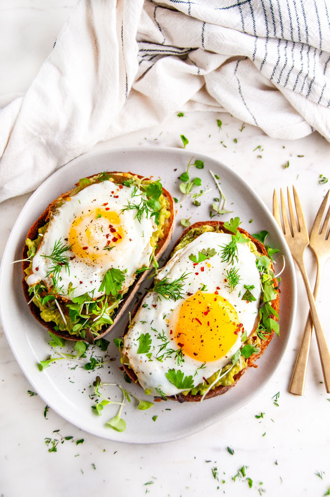 Avocado egg breakfast toast on gray plate with gold forks on white marble with tea towel