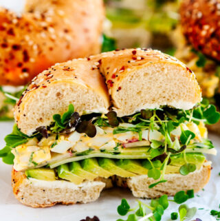 Avocado Egg Salad Bagel Sandwich half on parchment and white marble