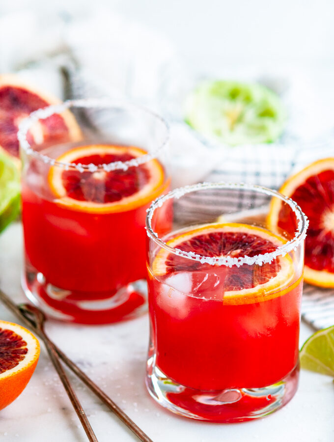 Blood Orange Margaritas on the rocks with limes and tea towel on white marble