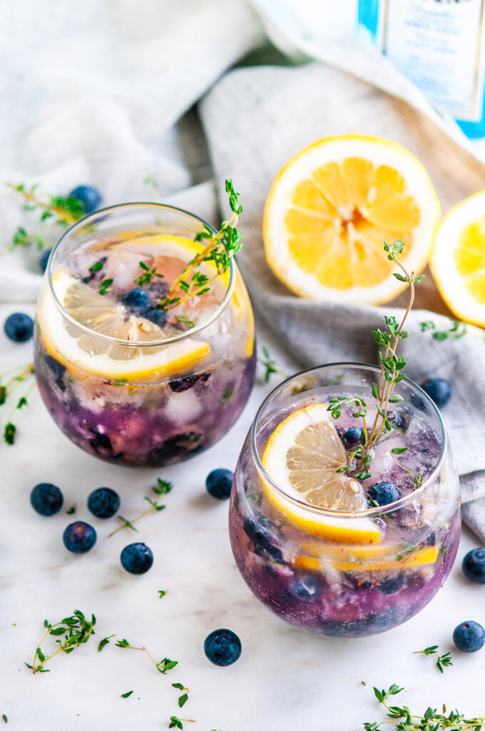 Blueberry Thyme Gin Fizz with lemons and gray tea towel on white marble