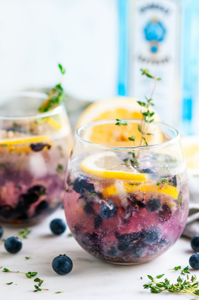 Blueberry Thyme Gin Fizz with lemons, gray tea towel and Bombay Sapphire gin on white marble