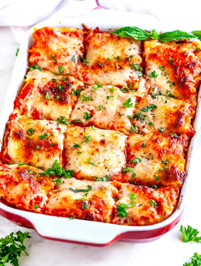 Garden Vegetable Lasagna in red and white casserole dish on white marble