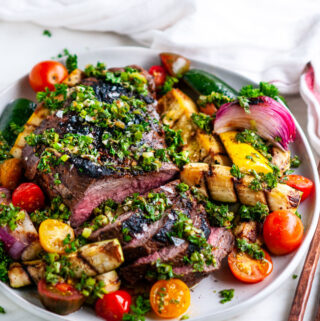 Grilled Tri Tip with Vegetables and Chimichurri Sauce on gray plate with copper silverware and tea towel