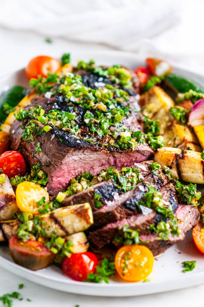 Grilled Tri Tip with Vegetables and Chimichurri Sauce on gray plate