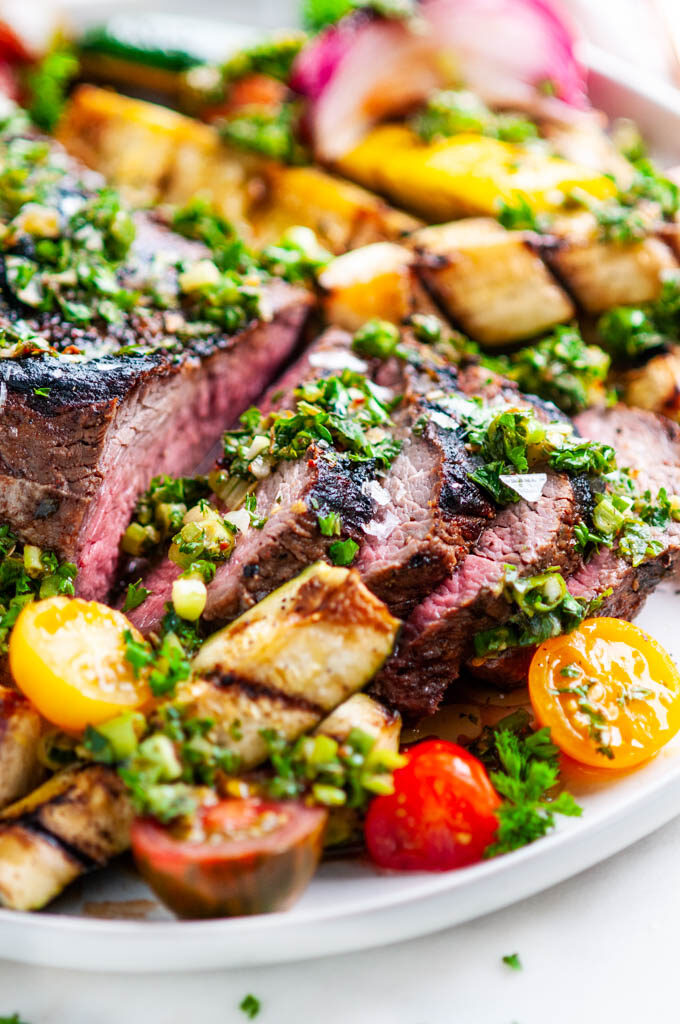 Grilled Tri Tip with Vegetables and Chimichurri Sauce on gray plate close up