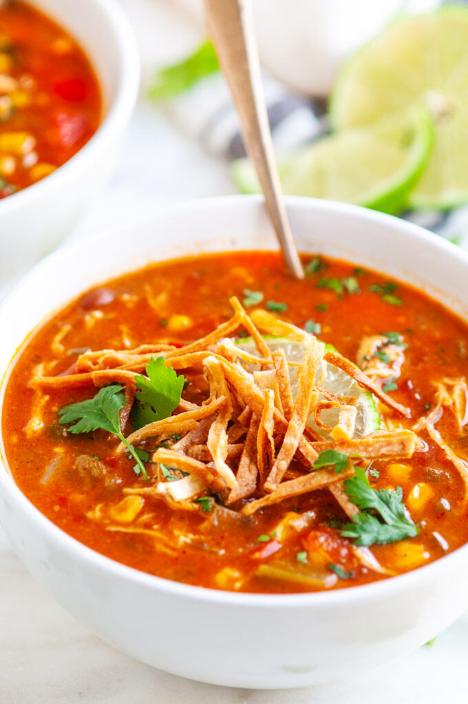 Slow Cooker Chicken Enchilada Soup with tortilla strips, lime and cilantro in white bowls on white marble