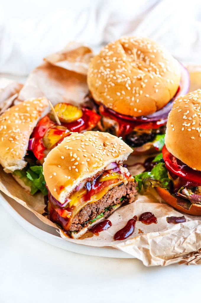 BBQ Cheddar Cheese Burgers on brown parchment and white marble