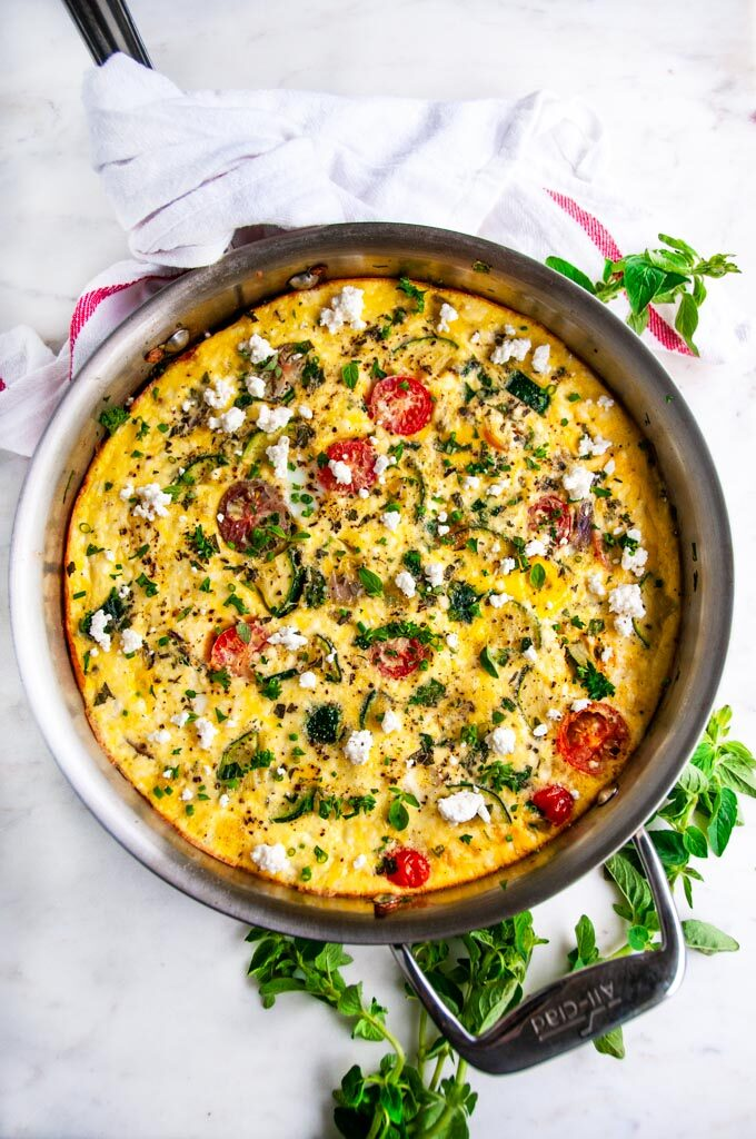 Greek Vegetable Frittata in all-clad skillet with oregano and tea towel on white marble