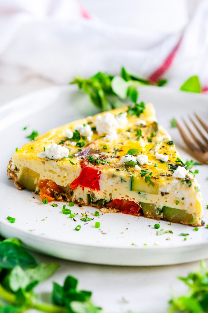 Greek Vegetable Frittata slice with gold fork and tea towel on white plate
