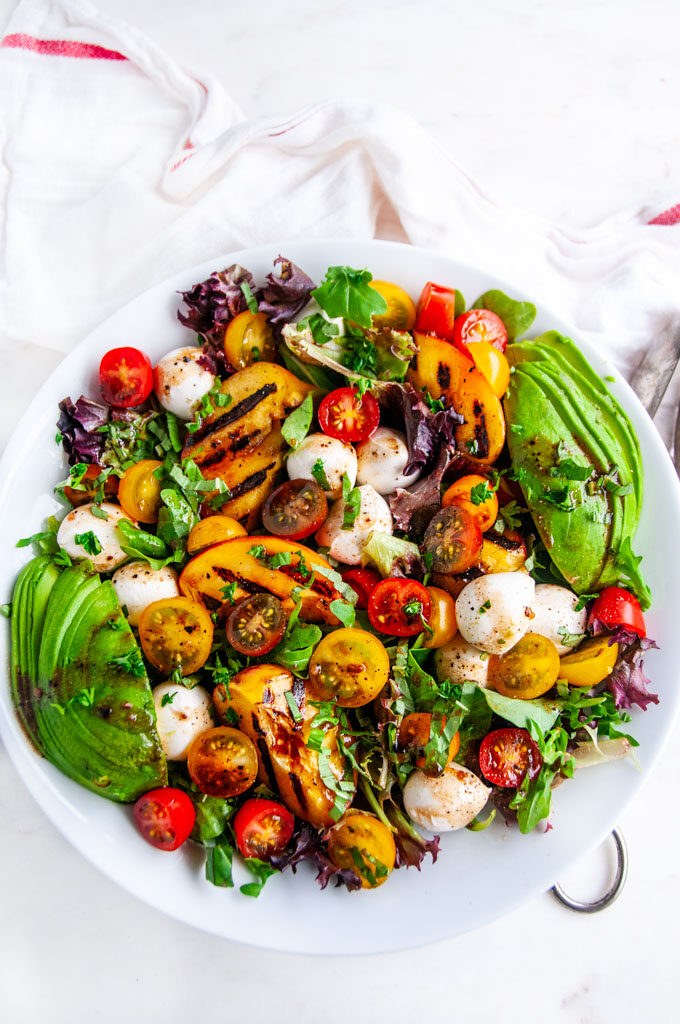 Grilled Peach Caprese Salad with avocado in white bowl on white marble