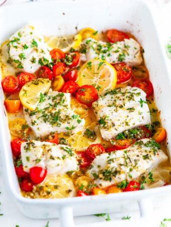 Lemon Herb Butter Baked Cod in white baking dish on white marble