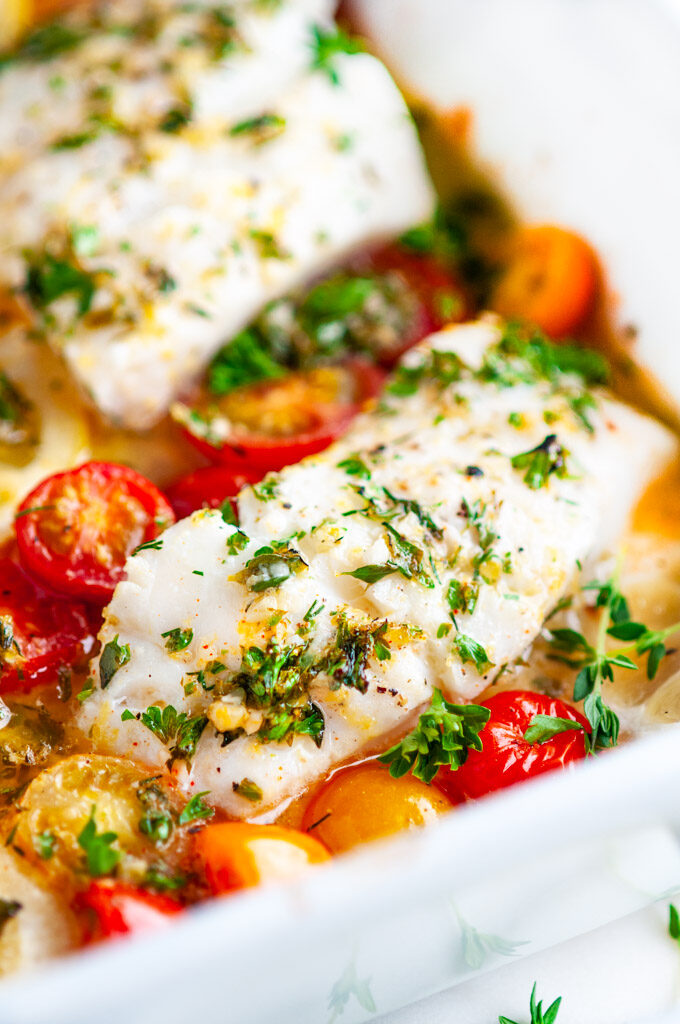 Lemon Herb Butter Baked Cod in white baking dish on white marble