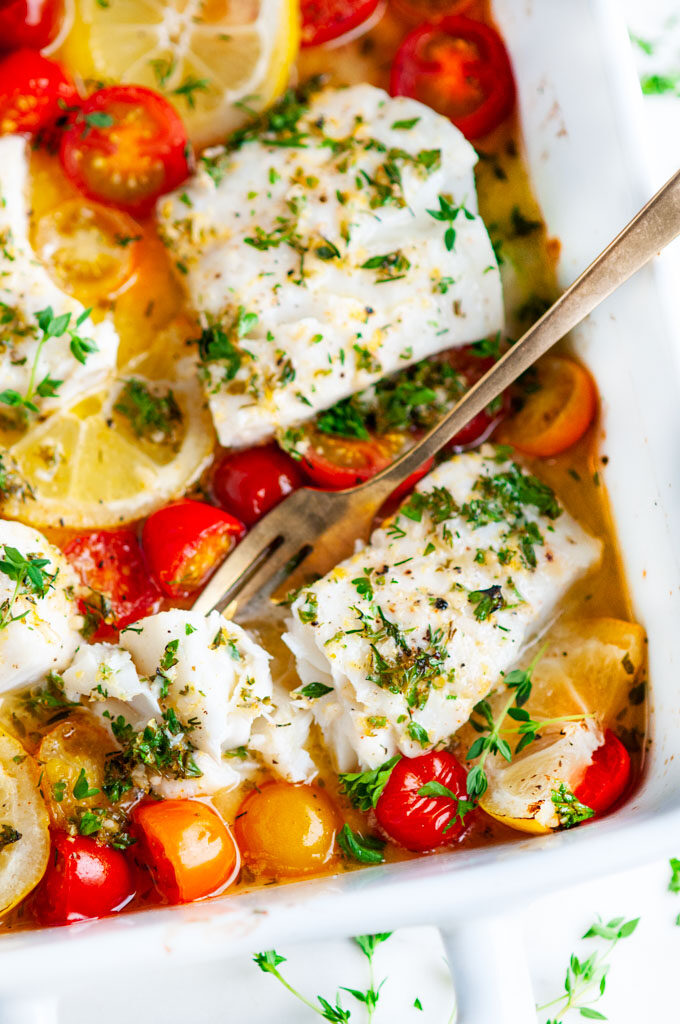 Lemon Herb Butter Baked Cod in white baking dish with gold fork