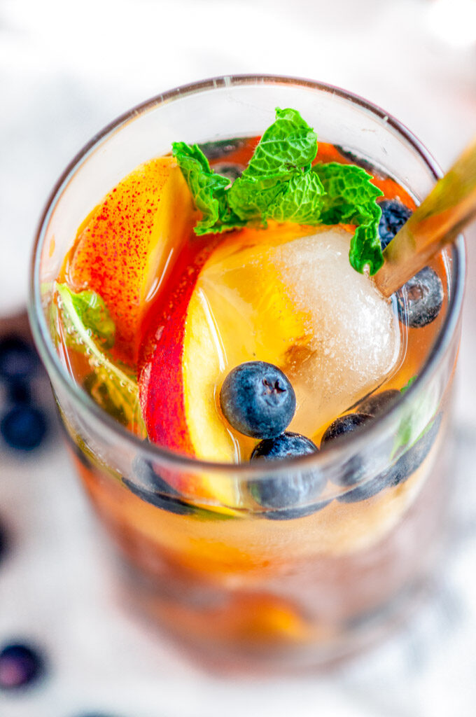 Sparkling Arnold Palmer Sangria glass with blueberries, peaches, mint, and gold spoon