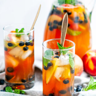 Sparkling Arnold Palmer Sangria pitcher and glasses with blueberries, peaches, mint, and gold spoons