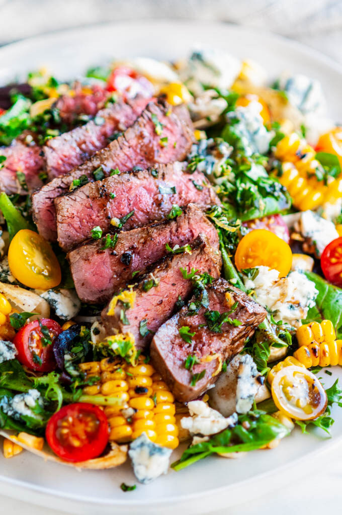 Balsamic Steak Gorgonzola Salad with Grilled Corn on white plate on white marble