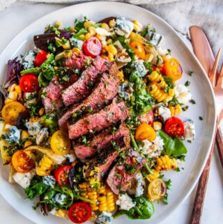 Balsamic Steak Gorgonzola Salad with Grilled Corn on white plate with copper silverware and tea towel on white marble