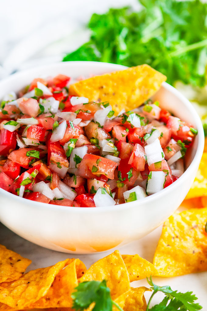 Classic Pico de Gallo salsa with chips and cilantro in white bowl