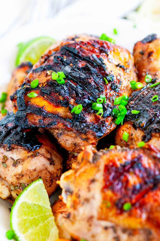 Grilled Jamaican Jerk Chicken with green onion and lime slices on white platter