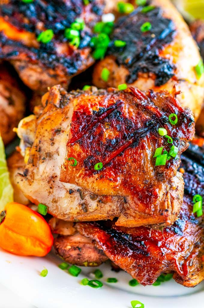 Grilled Jamaican Jerk Chicken with green onion, habanero peppers, and lime slices close up