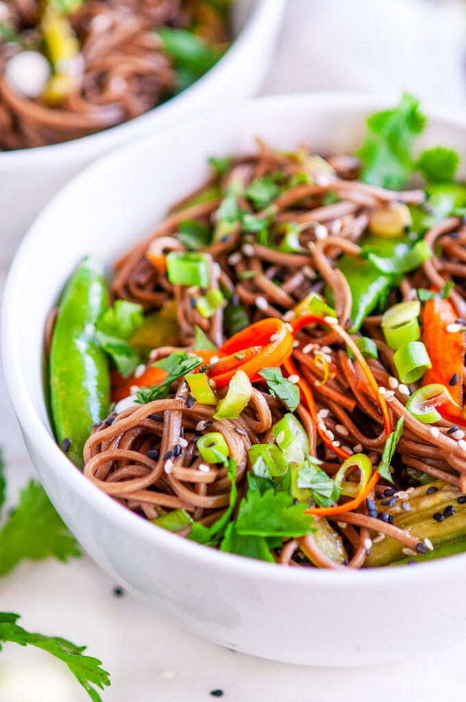 Soba Noodle Salad with Sesame Soy Dressing white bowl with cilantro, and tea towel