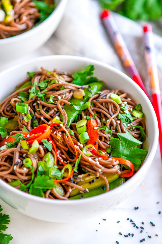 Soba Noodle Salad with Sesame Soy Dressing white bowl with cilantro, tea towel, and red chopsticks