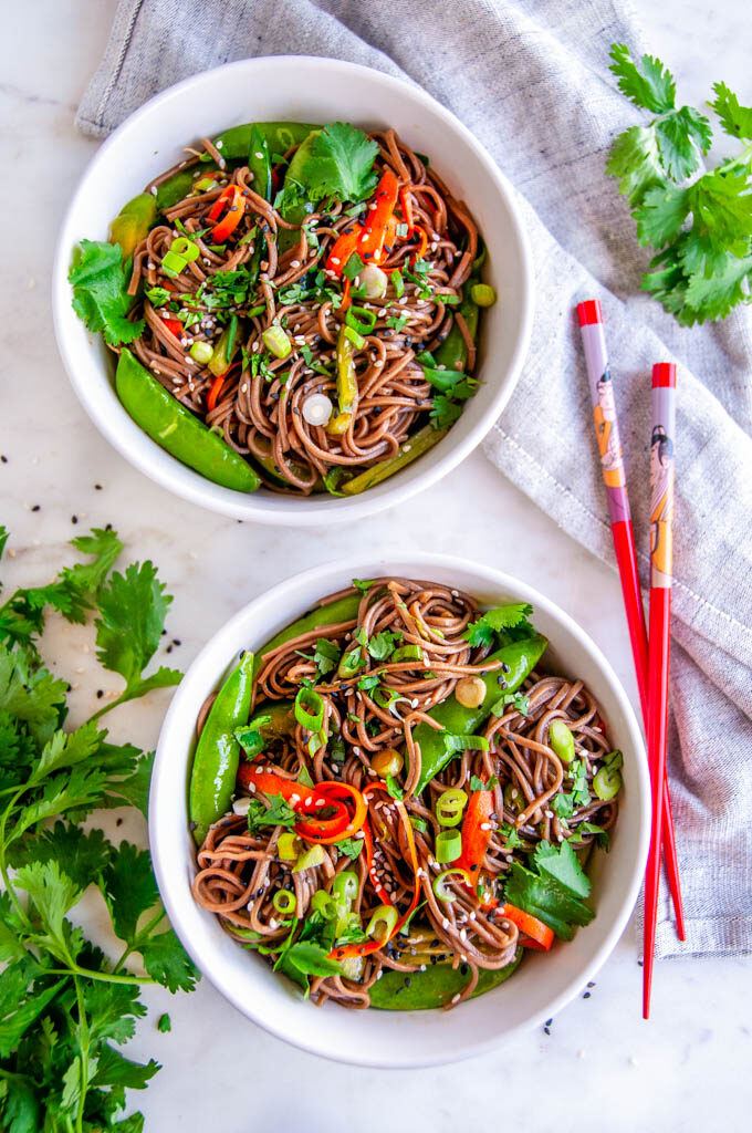 Soba Noodle Salad with Sesame Soy Dressing white bowls with cilantro, tea towel, and red chopsticks